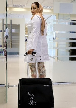 Manzil female physician in while laboratory coat pulling her trolley bag while also holding a stethoscope