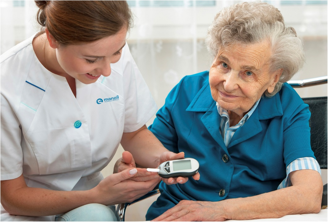 Manzil Health nurse doing a sugar finger test on elderly woman