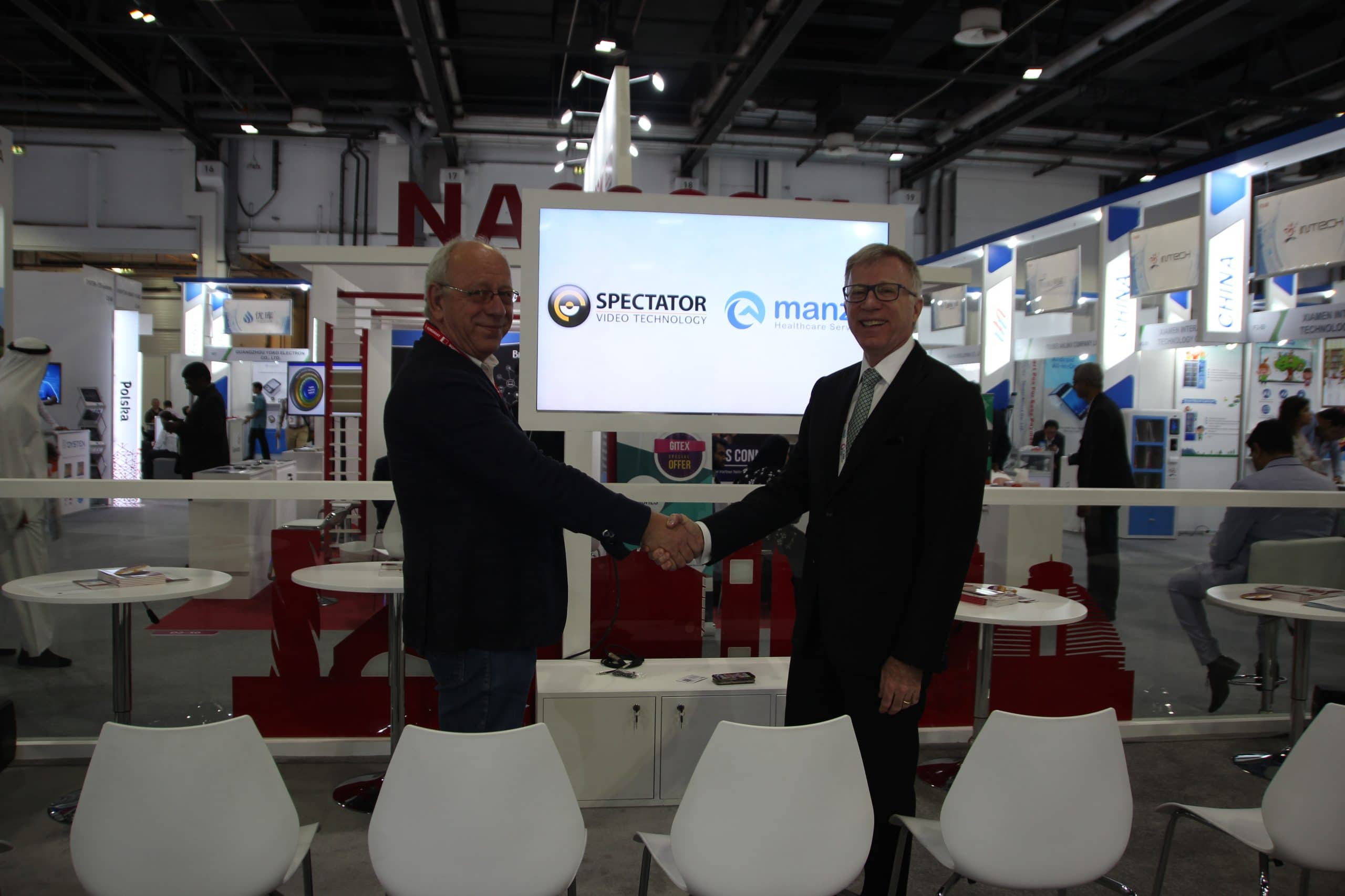 manzil and spectator video technology representatives shaking hands during a photo op