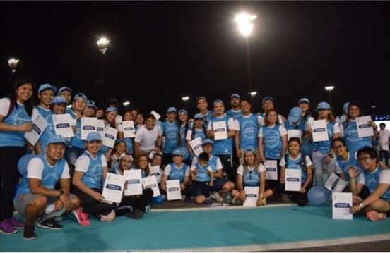 Manzil team in Bluevember walkathon shirts holding their certificates at during a photo op