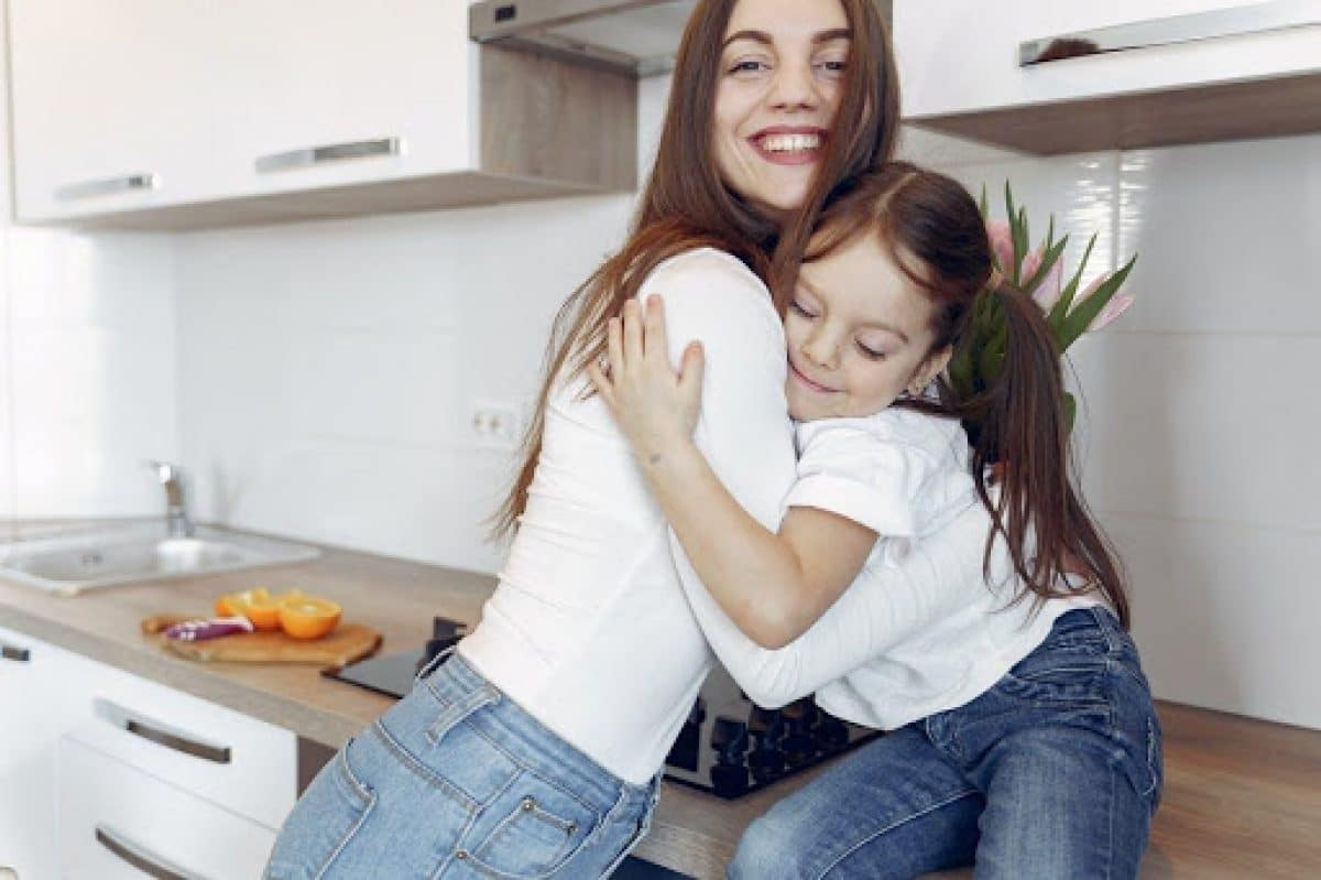 mother and child in white top and blue jeans hugging each other in the kitchen