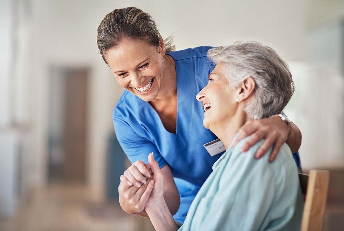 Manzil nurse in uniform and elderly patient laughing and holding hands