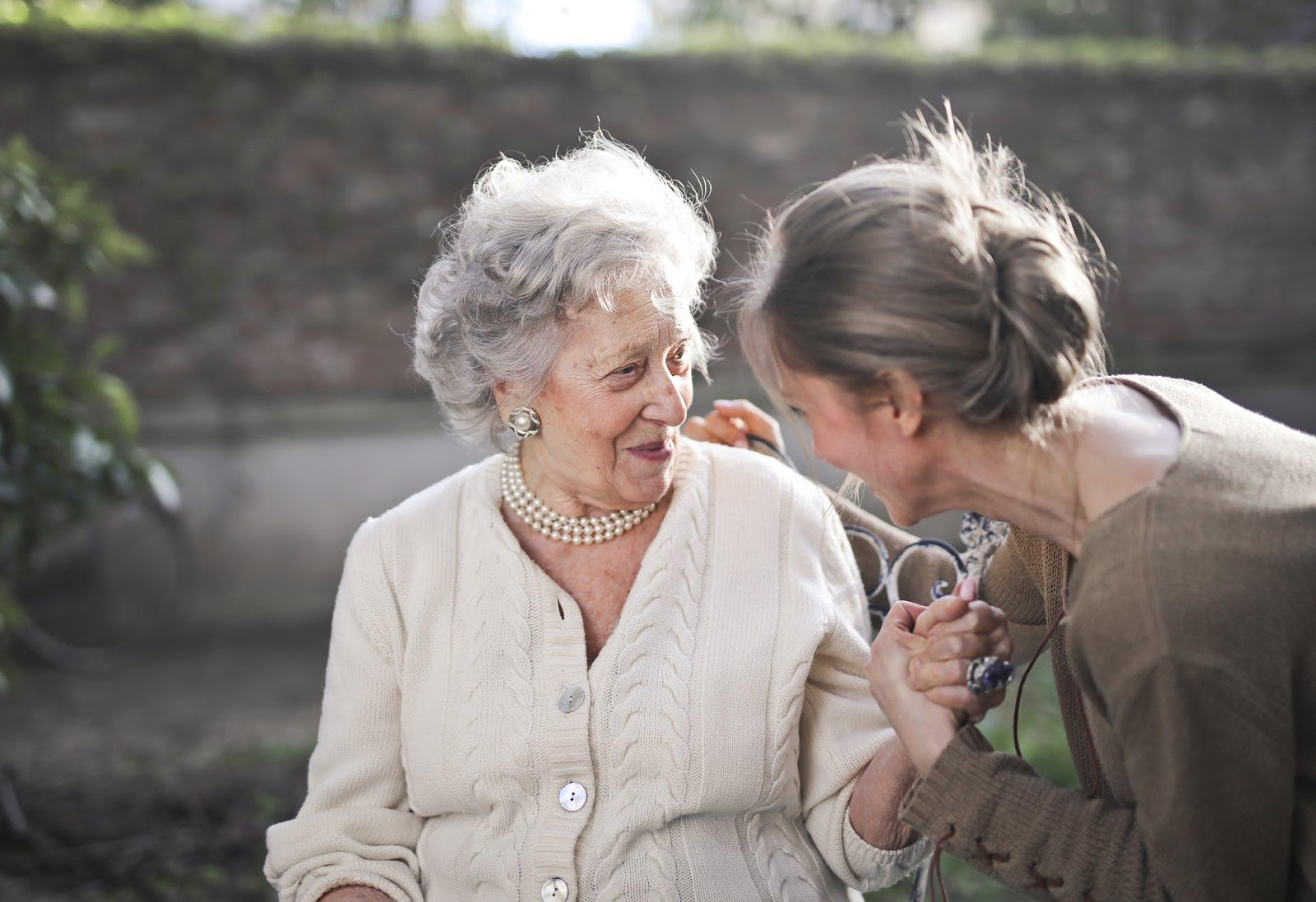 An elderly woman smiles at her caregiver