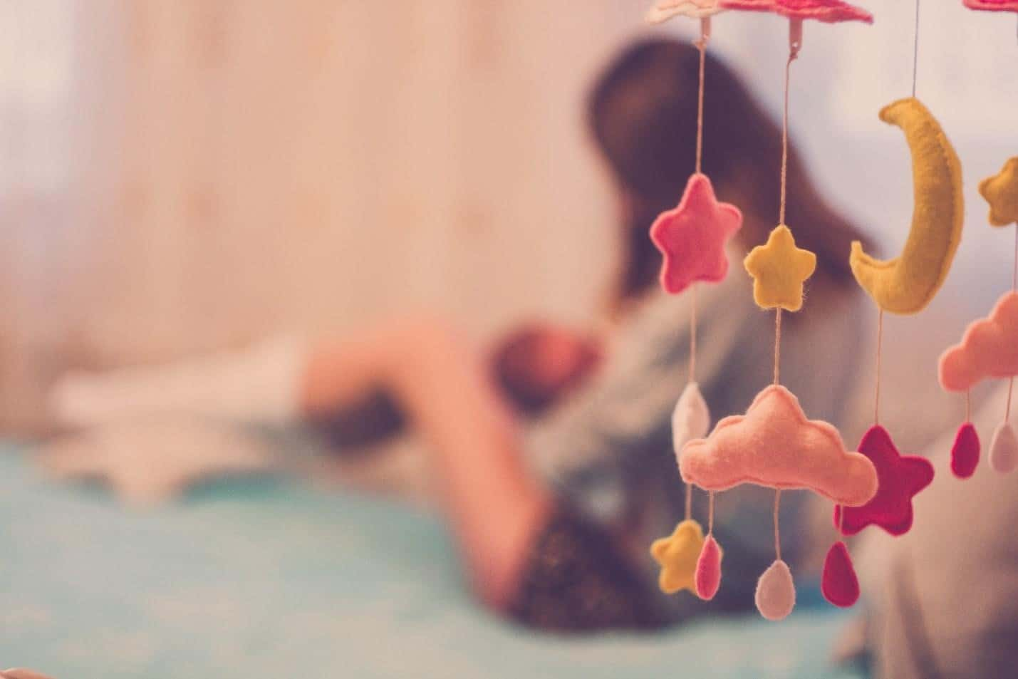 hanging colorful baby toys with the mother and baby at the background