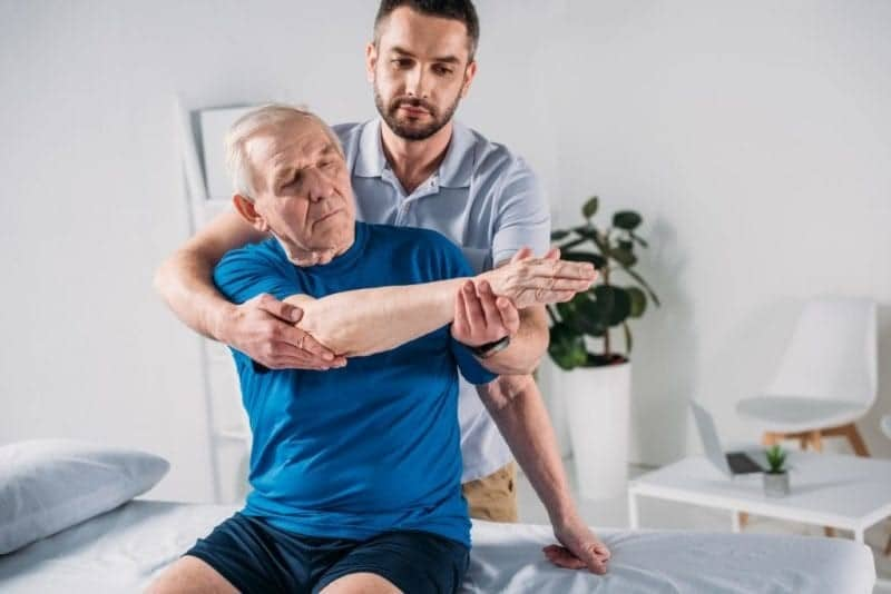 elderly man and physiotherapist during a therapy session