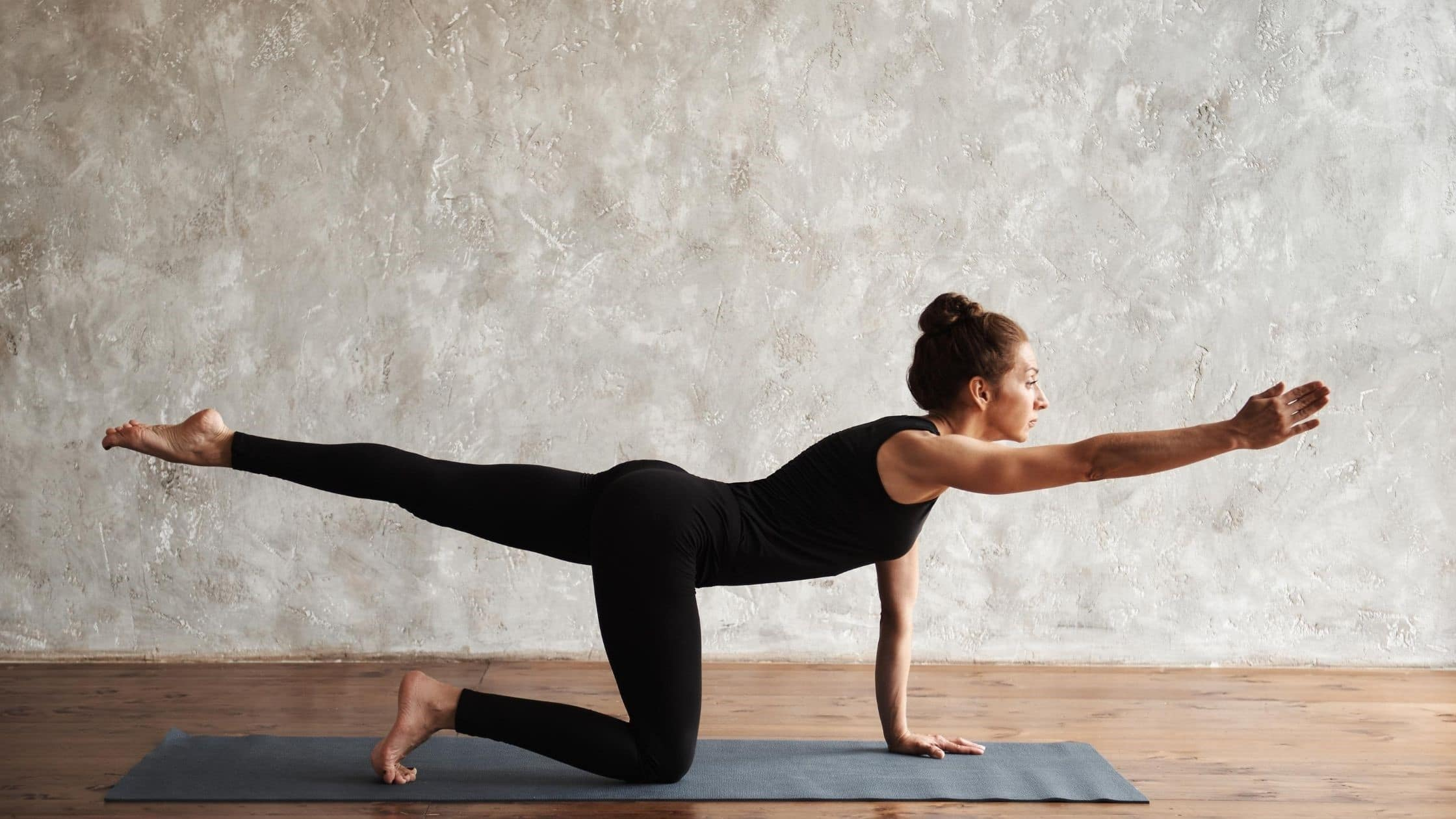 woman in black exercise outfit doing yoga