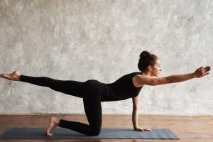 a woman doing a bird dog pose for back pain